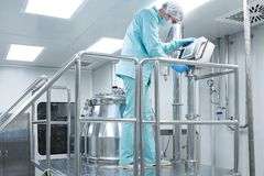 Pharmaceutical factory man worker in protective clothing operate production line in sterile working conditions. Pharmaceutical technician in sterile environment Stock Photo