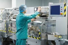 Pharmaceutical factory man worker in protective clothing operating production line in sterile environment. Pharmaceutical technician in sterile working Stock Images