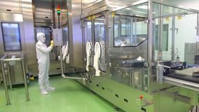 Pharmaceutical worker operating pharmaceutical equipment at pharmacy factory. Pharmaceutical manufacturing control
