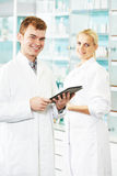 Pharmaceutical workers in drugstore Stock Images