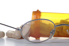 Pharmaceuticals. A pair of glasses in front of a pill bottle and pills stock photos