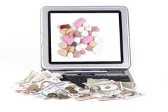 Pharmaceuticals. Tablet pc showing pharmaceuticals on screen, with bank notes of various currencies on white background Stock Image