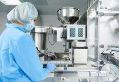 pharmaceutics Den farmaceutiska arbetaren fungerar den förpackande maskinen för blåsan royaltyfria foton