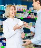 Pharmaceutist  helping customer. Female pharmaceutist in drugstore helping customer 25s to choose medication Royalty Free Stock Photos