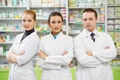 Pharmaceutist kvinna- och manarbetare i apotek arkivbild