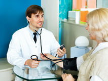 Pharmaceutist taking  mature patients blood pressure using  sphy Royalty Free Stock Image