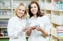 Pharmaceutist woman and man workers in drug store Stock Image