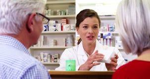 Pharmacien aidant la bouteille de la drogue aux clients banque de vidéos