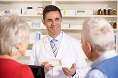 Pharmacien américain avec les couples aînés dans la pharmacie images libres de droits