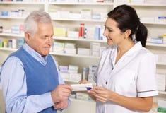 Pharmacien américain servant l'homme aîné dans la pharmacie photo stock