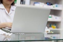 Pharmacien avec l'ordinateur portable et le médicament Photo stock