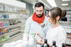 Pharmacien avec le client dans le magasin de pharmacie Image libre de droits