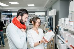 Pharmacien avec le client dans le magasin de pharmacie Photographie stock libre de droits