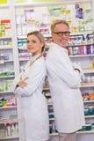 Pharmacien avec son stagiaire se tenant avec des bras croisés photo libre de droits
