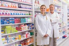 Pharmacien avec son stagiaire se tenant et souriant à l'appareil-photo image stock