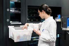 Pharmacien choisissant les meilleures médecines pendant le travail dans la pharmacie image stock