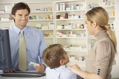 Pharmacien dans la pharmacie avec la mère et l'enfant photos libres de droits