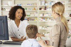 Pharmacien dans la pharmacie avec la mère et l'enfant images libres de droits