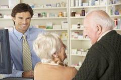 Pharmacien dans la pharmacie avec les couples supérieurs Photos stock