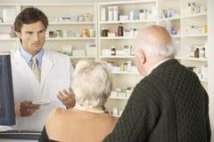 Pharmacien dans la pharmacie avec les couples supérieurs Photographie stock libre de droits
