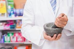 Pharmacien dans le manteau de laboratoire mélangeant une médecine images stock