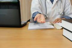 pharmacien de médecin de docteur portant le manteau médical de robe avec le stéthoscope tenant des pilules de comprimés photo libre de droits
