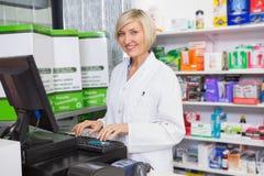Pharmacien de sourire à l'aide de l'ordinateur images stock