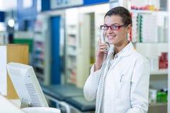Pharmacien de sourire parlant au téléphone dans la pharmacie images stock