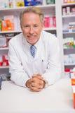 Pharmacien de sourire posant sur le bureau Photo libre de droits