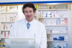 Pharmacien de sourire se tenant au compteur dans la pharmacie photographie stock libre de droits