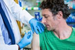 Pharmacien donnant l'injection au patient photographie stock libre de droits