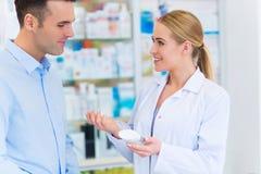 Pharmacien et client à la pharmacie image stock