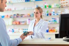 Pharmacien et client à la pharmacie photos stock