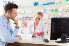 Pharmacien et client à la pharmacie images stock