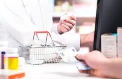 Pharmacien et client au compteur de pharmacie photographie stock