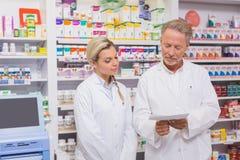 Pharmacien et stagiaire parlant ensemble au sujet de la prescription photographie stock libre de droits