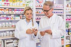 Pharmacien et stagiaire parlant ensemble au sujet du médicament image stock