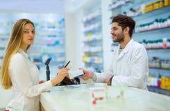 Pharmacien expérimenté conseillant le client féminin images libres de droits