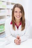 Pharmacien féminin amical se penchant sur le compteur images libres de droits