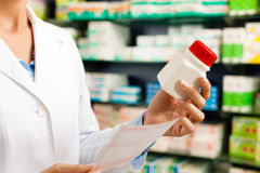 Pharmacien féminin dans la pharmacie avec du médicament Image stock