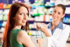 Pharmacien féminin dans sa pharmacie avec un propriétaire Image libre de droits