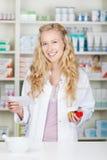Pharmacien féminin Holding Prescription Paper et bouteille de pilule Photos libres de droits