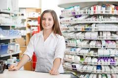 Pharmacien féminin restant au compteur photo stock