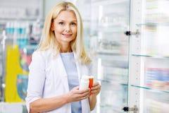 pharmacien féminin tenant des récipients avec des médicaments et le sourire photo stock