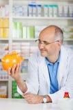 Pharmacien Holding Piggybank While se penchant sur le compteur Photographie stock