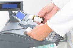 Pharmacien à l'aide de la caisse enregistreuse Image stock