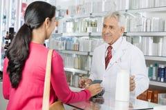 Pharmacien Looking At Female effectuant le paiement de NFC pour le shampooing photographie stock