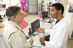 Pharmacien masculin de jeune mulâtre parlant avec un client Photographie stock libre de droits