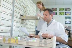 Pharmacien masculin professionnel rassemblant la prescription dans le bas-côté photos stock