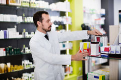 Pharmacien masculin recherchant la bonne médecine Photo stock